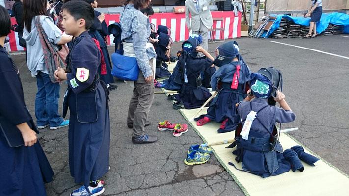 境内で面をつける小学生