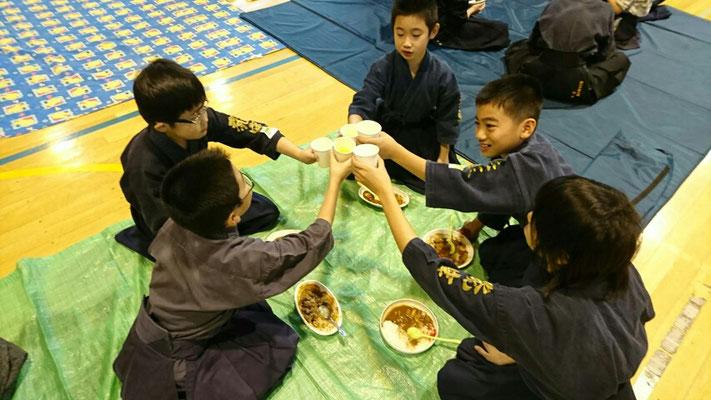 お茶で乾杯する小学生