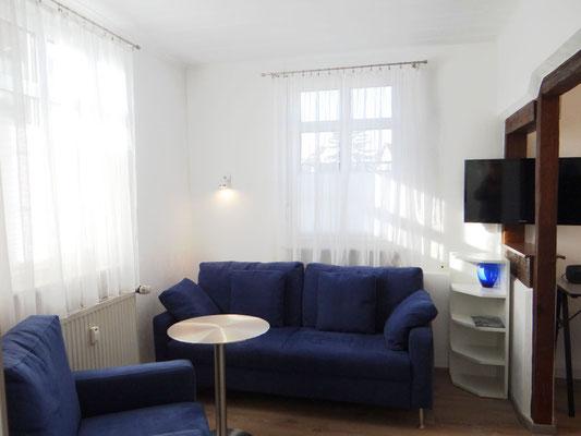 Sitzgelegenheiten mit Couch und Sessel für längerfristiges Wohnen.