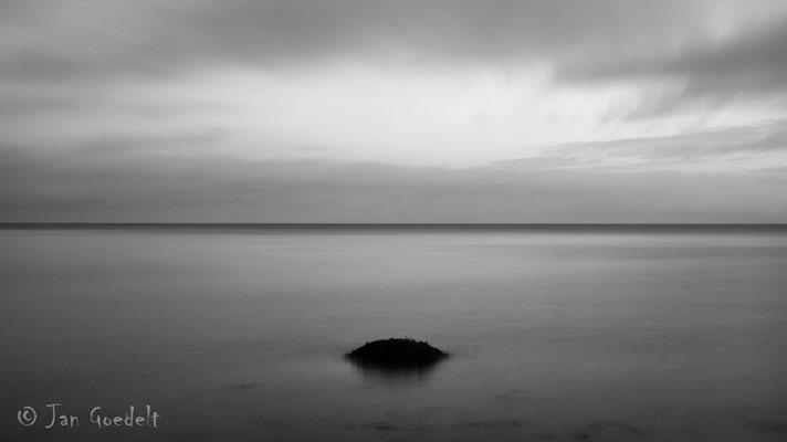 Stein in der Ostsee unter einem Wolkenloch, Schleswig-Holstein