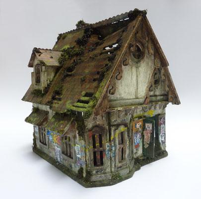 <b>Haus</b><br />2019<br />Holz, Acrylfarbe, Modelgras, Irisch Moss<br />  31,5 cm x 32 cm x 23 cm