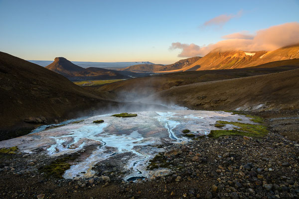 A look from a colourful hot spring towards the sunlit mountains Kolufell and Skrauti. Far in behind the Hamarinn protrude from the ice of Vatnajökull.