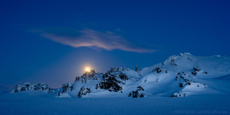 Moonset behind Bræðrafell and a landscape illuminated by the twilight.