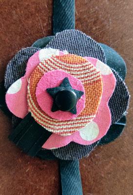 fleur de botte ou bracelet dans les tons orange, noir et fushia.
