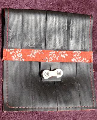 porte monnaie en chambre à air de vélo décoré de tissu à motifs oranges et fermé par un maillon de chaine