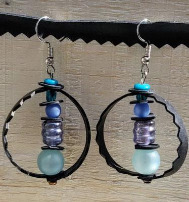 Boucle d'oreille pendentif ornée d'un cercle de chambre à air composée d'un mélange de perles dans les tons bleus.