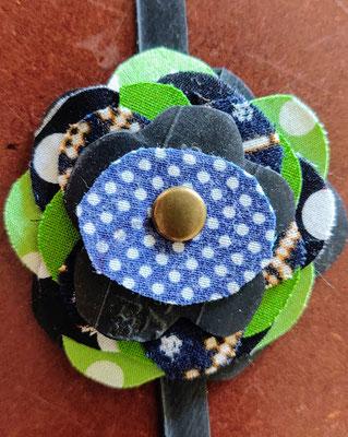 fleur de botte ou bracelet dans les tons vert, noir et bleu.