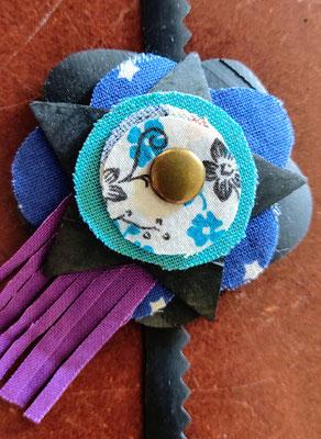 fleur de botte ou bracelet dans les tons bleu et violet.