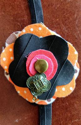 fleur de botte ou bracelet dans les tons orange, rouge et fushia.
