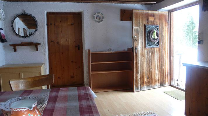 Wohnraum mit Blick zur Eingangstür und Zugang zum Doppelzimmer