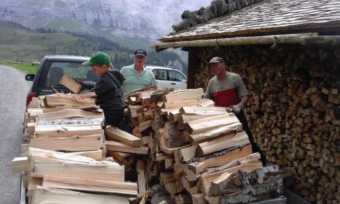 Das Brennholz für den nächsten Sommer wird gerüstet und zum Trocnen an der Spycherwand aufgeschichtet.