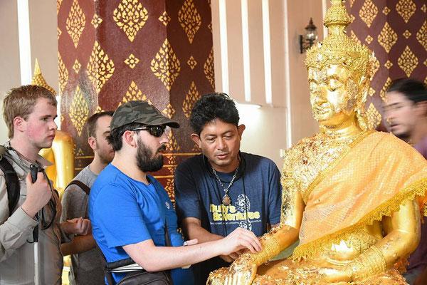 Goldplättchen auf einer Buddhastatue ertasten