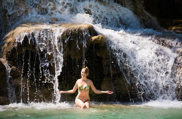 Junge Frau badet in einem Wasserfall im thailändischen Regenwald