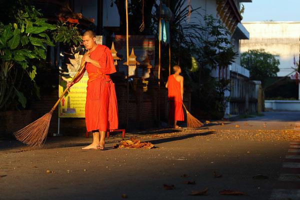 Typisches thailändisches Bild: Mönche beim fegen am Tempel