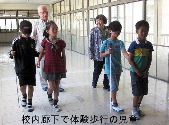 校内廊下をアイマスク体験する児童