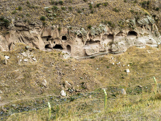 numerous caves dug into cliffs, as well as fortifications. A modern border fence can be seen at bottom center