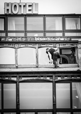Tbilisi, Georgia - a clerk cleans the outside windows of the Kopala Hotel very adventurously