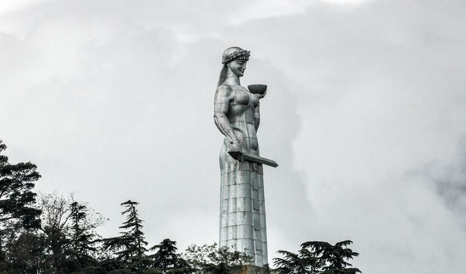 Kartlis Deda, or Mother Georgia. She symbolizes the Georgian national character: in her left hand she holds a bowl of wine to greet those who come as friends, and in her right hand is a sword for those who come as enemies