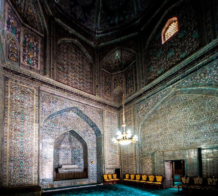 The entire interior is covered in blue and green majolica tiling with distinctive motifs complemented by rich gold borders