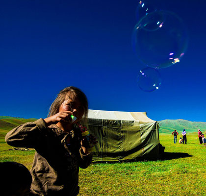 Perizat blows shimmering soap bubbles
