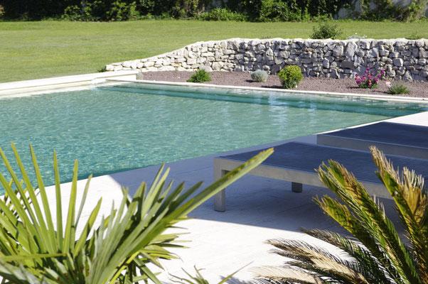 les plantations au fond de la piscine et le muret de pierres sèches