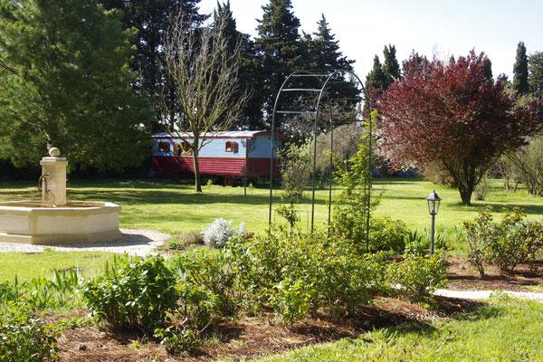 Le parc, la fontaine et la roulotte au fond