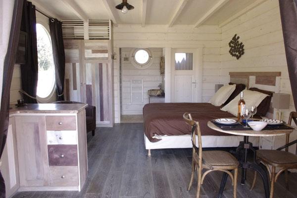 l'intérieur de la cabane, le lit king size de 180  x 200 cm