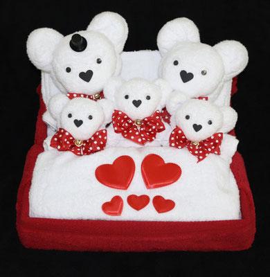 Handtuchfiguren als Hochzeitspaar mit Drillingen im Bett