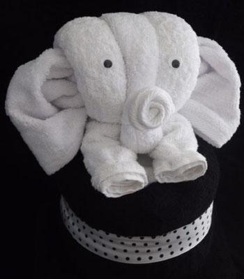 Handtuchfigur als weißer Elefant, bestehend aus einem Handtuch, zwei Gästehandtüchern und einem schwarzen Duschtuch