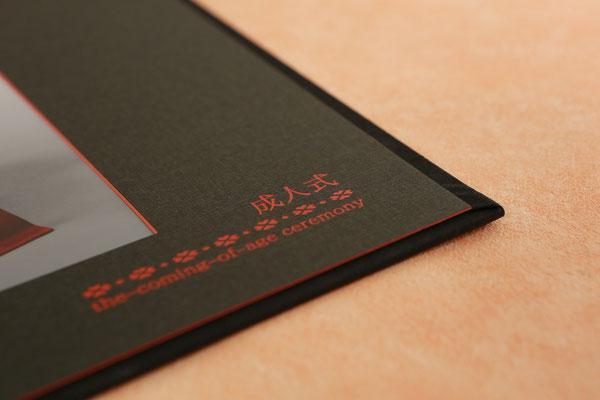 写真を引き立てる赤の縁どりと レリーフ彫りのワンポイント