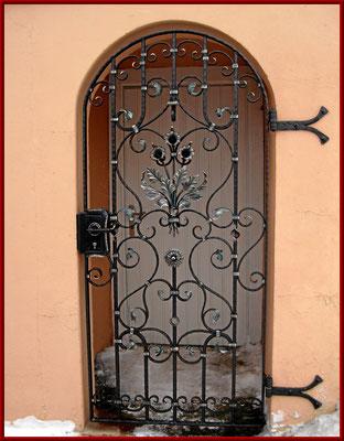 geschmiedete Eingangstür mit einem Blumenstrauß