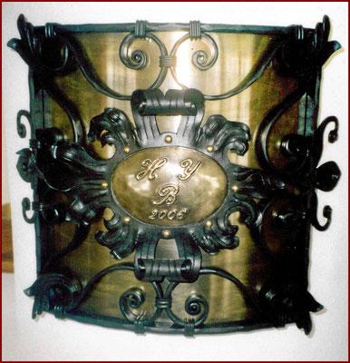 geschmiedetes Ziergitter zur Rauchrohrabdeckung mit Bronze hinterlegt und eingetriebenen Initialen