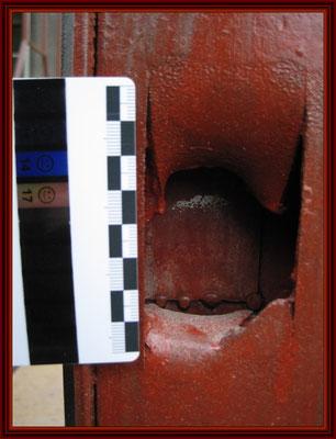 Loch des durchgegangenen Granatsplitters mit Vergleichsmaßstab fertig konserviert