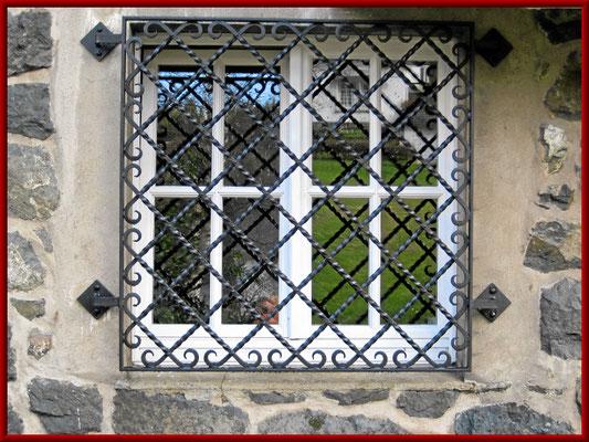 Fenstergitter als Einbruchschutz von Quadrateisen gedreht, vernietet an den Kreuzungspunkten, Enden geschmiedet
