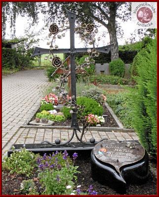 geschmiedetes Grabkreuz mit einer Rosenranke aus Schmiedebronze mit einer getriebenen Schrifttafel