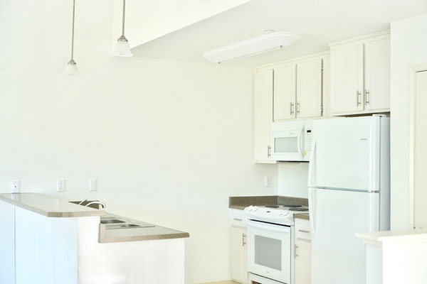 a closeup of the updated, modern, and open-space galley kitchen with white cabinetry