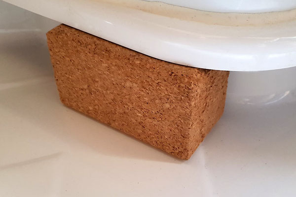 Sicher ist sicher: Gut passende Abstützung des drehbaren (und dann frei schwebenden und bedenklich knarzenden) Toilettensitzes. Es sind zwei zusammengeklebte Schleifblöcke aus Kork - passt optimal!