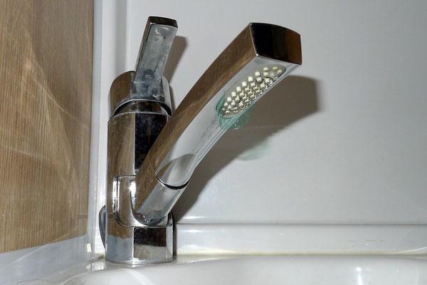 Tropfenfänger aus einem Stück einer PET-Flasche verhindert das Zurücklaufen von Wasser durch die Steckvorrichtung unter das Waschbecken. Die Brause ist im Zusammenhang mit der Mischbatterie (entschuldigt den Dreck!) diesbezüglich eine Fehlkonstruktion