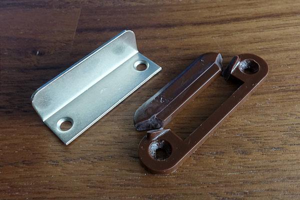 Der abgebrochene Schließwinkel der Badezimmertür und der neue aus Metall. Warum wird das nicht ab Werk so geliefert?