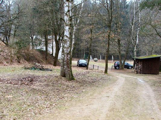 Blick vom Schützenhaus zum Parkplatz, rechts erkennt man den alten Kaminholz-Unterstand. April 2016
