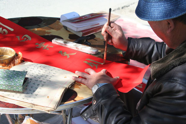 Man painting banners for Chinese New Year - Dali