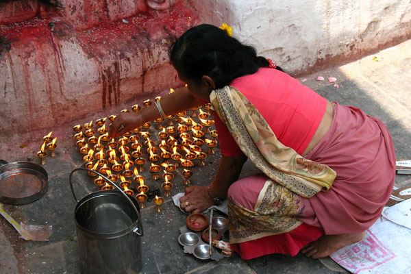 Woman lighting butter lamps - Bodnath Stupa - Kathmandu
