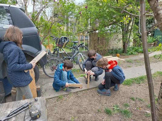Les enfants arrachent les clous des morceaux de palettes