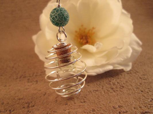 Glasfläschchen in Metallspirale