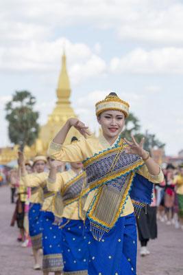 Festliche Prozession mit traditionell gekleideten Tänzerinnen.