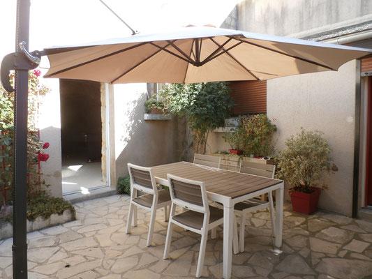 Un grand parasol peut ombrager toute la cour.