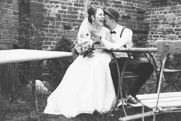 Hochzeitsfotograf Berlin - Hochzeitsfotografie lachendes Brautpaar im Hof des Haus am Bauernsee Dobbrikow