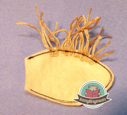 Cut out the ear and sew some loops from embroidery thread at the upper edge. Sew around the edge.