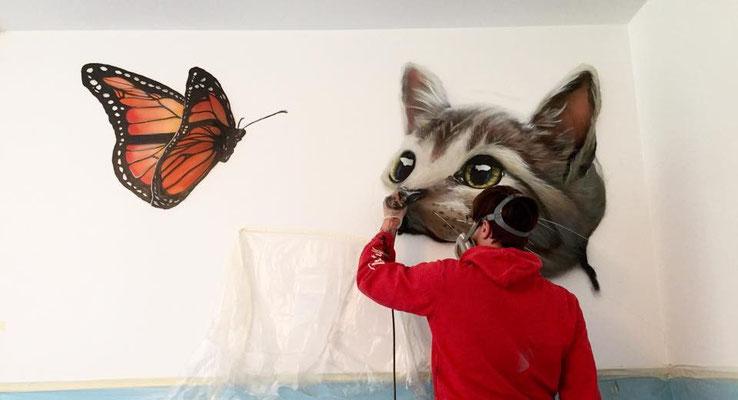 Graffiti Künstler live an der Wand bei der Wandgestaltung im Innenraum Hansestadt