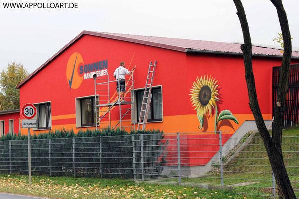 Firmenfassade Wandgestaltung und Fassadengestaltung mit Wandbild und Firmenlogo gestaltet in Fürstenwalde mit der Graffiti Kunst im schönen Brandenburg Oder Spree. Solar Solaranlage.Empfangsbereichgestaltung